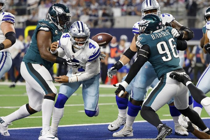 Philadelphia Eagles defensive tackle Fletcher Cox (91) helps strip the ball away from Dallas Cowboys quarterback Dak Prescott (4) in the end zone as defensive end Derek Barnett (96) looks on in the first half of an NFL football game in Arlington, Texas, Monday, Sept. 27, 2021. Cox recovered the fumble for a Eagles touchdown. (AP Photo/Michael Ainsworth)