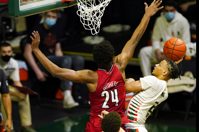 Miami guard Isaiah Wong (2) drives to the basket as Louisville forward Jae'Lyn Withers (24) defends, during the second half of an NCAA college basketball game, Saturday, Jan. 16, 2021, in Coral Gables, Fla. (AP Photo/Marta Lavandier)