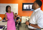 In this Wednesday, Aug. 29, 2018 photo, Jahana Hayes, left, Democratic nominee for Connecticut's 5th Congressional District, speaks with her campaign manager, Michael Bland, in her Waterbury, Conn. campaign headquarters. Hayes, a former National Teacher of the Year, will face Republican Manny Santos in the November general election. (AP Photo/Susan Haigh)