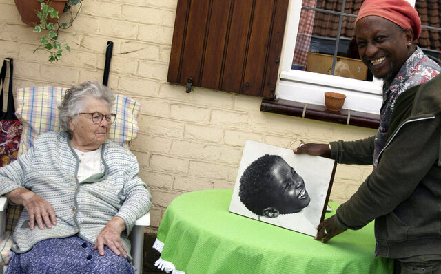 In this photo taken on Monday, June 22, 2020, Eric Baranyanka, right, and his foster mother Emma Monsaert look at a photo of Eric as a young boy in Lembeek, Belgium. Baranyanka fled political persecution in the Belgian protectorate of Burundi in the 1960's, landing half a world away at a military airport in Brussels, before being fostered by Emma Monsaert and her husband Paul. (AP Photo/Virginia Mayo)