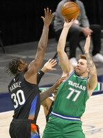 Dallas Mavericks guard Luka Doncic (77) shoots the ball as New York Knicks forward Julius Randle (30) goes up to defend during the first half of an NBA basketball game, Friday, April 16, 2021, in Dallas. (AP Photo/Ron Jenkins)