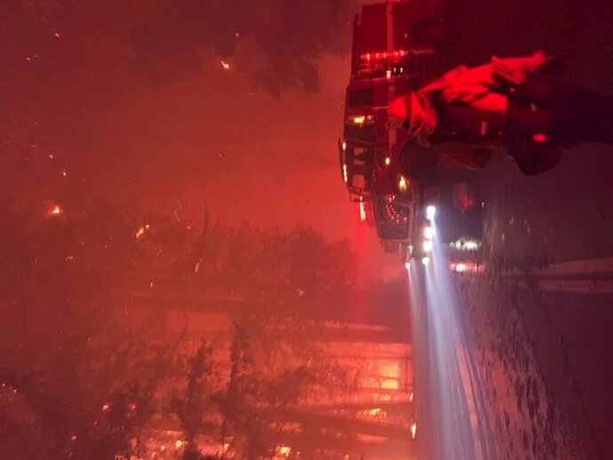 In this Aug. 18, 2020, photo provided by Justin Silvera, firefighters with Cal Fire, the California state firefighting agency, fight a blaze in Big Basin Redwoods State Park on a night in which they saved two stranded citizens in the park. Deadly wildfires in California and the Pacific Northwest have strained the human and equipment resources barely halfway into the wildfire season. (Justin Silvera/Cal Fire Local 2881 via AP)