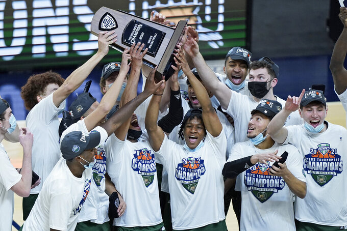 Ohio teammates celebrate after they defeated Buffalo in an NCAA college basketball game in the championship of the Mid-American Conference tournament, Saturday, March 13, 2021, in Cleveland. (AP Photo/Tony Dejak)