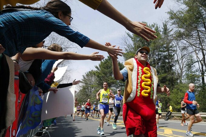 FILE -- In this April 15, 2013, file photo, a man dressed as a hot dog runs through Wellesley, Mass., during the 117th running of the Boston Marathon. Due to the COVID-19 virus pandemic, the 124th running of the Boston Marathon was postponed from its traditional third Monday in April to Monday, Sept. 14, 2020. (AP Photo/Michael Dwyer, File)