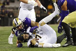 California quarterback Chase Garbers, center, is sacked by Washington linebacker Laiatu Latu, left, during the first half of an NCAA college football game, Saturday, Sept. 7, 2019, in Seattle. (AP Photo/Ted S. Warren)
