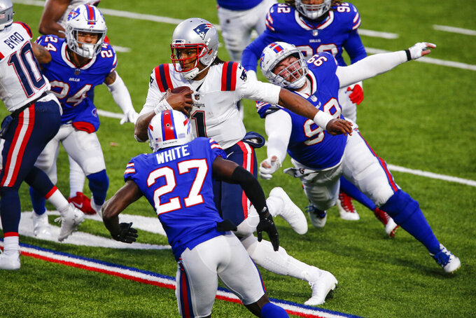 New England Patriots' Cam Newton (1) rushes past Buffalo Bills' Harrison Phillips (99) and Tre'Davious White (27) during the second half of an NFL football game Sunday, Nov. 1, 2020, in Orchard Park, N.Y. Newton fumbled the ball on the play. The Bills won 24-21. (AP Photo/John Munson)