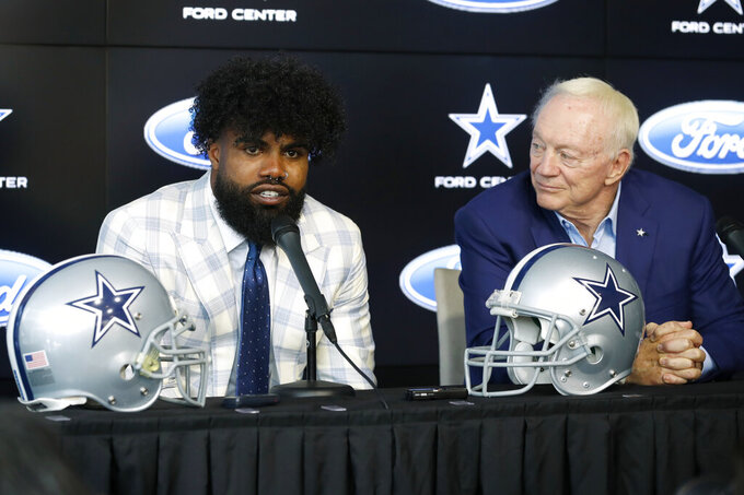 Dallas Cowboys running back Ezekiel Elliott, left, makes comments during a news conference about his new contract as team owner Jerry Jones, right, looks on at the NFL football team's practice facility in Frisco, Texas, Thursday, Sept. 5, 2019. (AP Photo/Tony Gutierrez)
