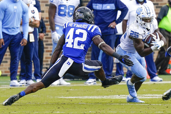 North Carolina running back Javonte Williams (25) runs away from Duke linebacker Shaka Heyward (42) during the second half of an NCAA college football game at Wallace Wade Stadium, Saturday, Nov. 7, 2020, in Durham, N.C. (Jim Dedmon/Pool Photo via AP)