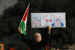 Palestinian hold poster depicting Israeli Prime Minister Benjamin Netanyahu, left, and US Secretary of State Mike Pompeo as clashes with Israeli troops broke out during the protest against the U.S. announcement that it no longer believes Israeli settlements violate international law., at checkpoint Beit El near the West Bank city of Ramallah, Tuesday, Nov. 26, 2019, (AP Photo/Majdi Mohammed)