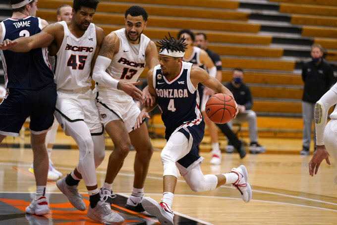 Gonzaga guard Aaron Cook (4) goes to the basket against Pacific's Nigel Shadd (45) and Jeremiah Bailey (13) during the second half of an NCAA college basketball game in Stockton, Calif., Thursday, Feb. 4, 2021. Gonzaga won 76-58. (AP Photo/Rich Pedroncelli)
