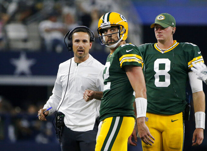 Green Bay Packers coach Matt LaFleur, left, talks with Aaron Rodgers (12) and Tim Boyle (8) on the sideline during the first half of the team's NFL football game against the Dallas Cowboys in Arlington, Texas, Sunday, Oct. 6, 2019. (AP Photo/Michael Ainsworth)