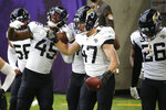 Jacksonville Jaguars linebacker Joe Schobert (47) celebrates with teammates after returning an interception 43-yards for a touchdown during the second half of an NFL football game against the Minnesota Vikings, Sunday, Dec. 6, 2020, in Minneapolis. (AP Photo/Bruce Kluckhohn)