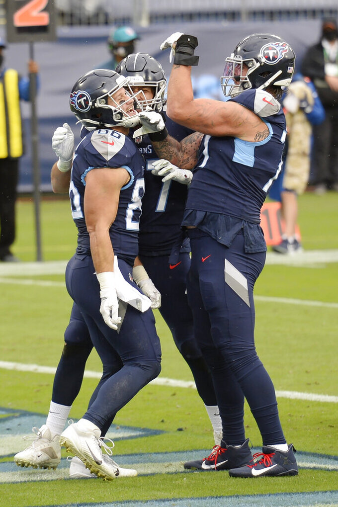 Tennessee Titans tight end Anthony Firkser (86) celebrates with offensive tackle Taylor Lewan, right, after Firkser caught a touchdown pass against the Houston Texans in the first half of an NFL football game Sunday, Oct. 18, 2020, in Nashville, Tenn. (AP Photo/Mark Zaleski)