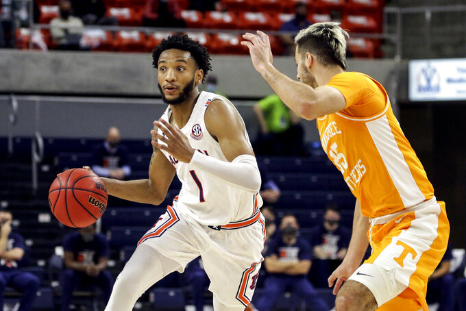 Auburn guard Jamal Johnson (1) brings the ball down court as Tennessee guard Santiago Vescovi (25) defends during the first half of an NCAA basketball game Saturday, Feb. 27, 2021, in Auburn, Ala. (AP Photo/Butch Dill)