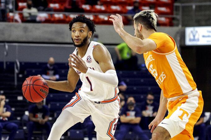 Auburn guard Jamal Johnson (1) brings the ball down court as Tennessee guard Santiago Vescovi (25) defends during the first half of an NCAA basketball game Saturday, Feb. 27, 2021, in Auburn, Ala. (AP Photo/Butch Dill)
