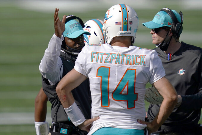 FILE - Miami Dolphins head coach Brian Flores, left, confers with quarterback Ryan Fitzpatrick in the second half of an NFL football game, Sunday, Sept. 13, 2020, in Foxborough, Mass. Fitzpatrick threw three interceptions in Miami's 21-11 loss at New England. (AP Photo/Charles Krupa, File)