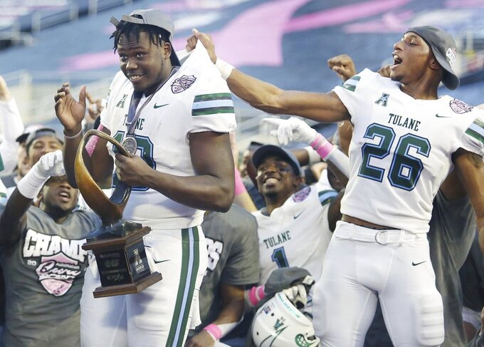 Tulane players Darius Bradwell (10) and Thakarius Keyes (26) celebrate after winning the Cure Bowl NCAA college football game against Louisiana in Orlando, Fla, on Saturday, Dec. 15, 2018. (Stephen M. Dowell/Orlando Sentinel via AP)