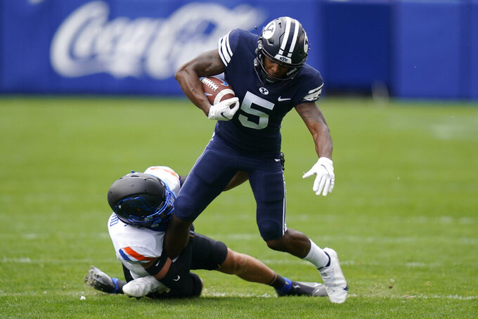 Boise State cornerback Kaonohi Kaniho, bottom, tackles BYU wide receiver Chris Jackson (5) in the first half during an NCAA college football game Saturday, Oct. 9, 2021, in Provo, Utah. (AP Photo/Rick Bowmer)