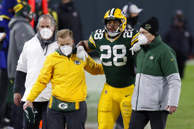 Green Bay Packers' A.J. Dillon is helped off the field during the second half of an NFL divisional playoff football game against the Los Angeles Rams Saturday, Jan. 16, 2021, in Green Bay, Wis. (AP Photo/Matt Ludtke)