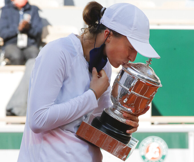 Poland's Iga Swiatek kisses the trophy after winning the final match of the French Open tennis tournament against Sofia Kenin of the U.S. in two sets 6-4, 6-1, at the Roland Garros stadium in Paris, France, Saturday, Oct. 10, 2020. (AP Photo/Michel Euler)