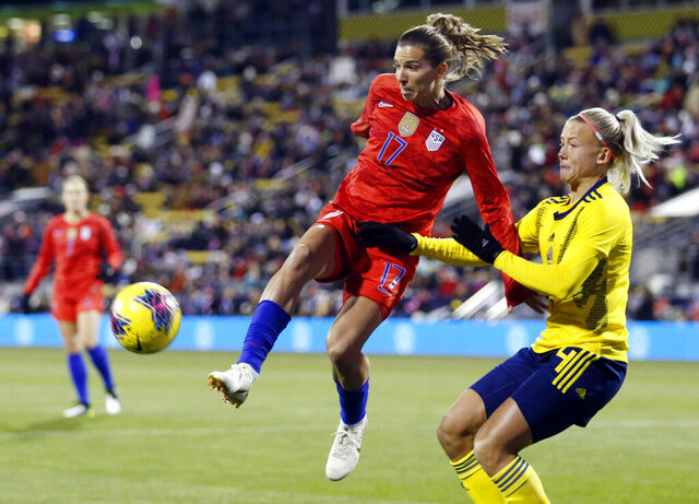 FILE - In this Thursday, Nov. 7, 2019 file photo, United States forward Tobin Heath, left, passes the ball in front of Sweden defender Hanna Glas during the first half of a women's international friendly soccer match in Columbus, Ohio. Tobin Heath will soon be hoping to play at Old Trafford again. The winger has more chance now she has signed for Manchester United, although the Women's Super League team has yet to play in the stadium that has been home to the men's side for 110 years. (AP Photo/Paul Vernon, File)