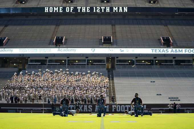 The Texas A&M University Yell Leaders kneel at midfield as part of the first Midnight Yell Practice this season in Kyle Field, College Station, Texas early Saturday, Sept. 26, 2020. . Due to Coronavirus restrictions, the Texas A&M Band were the only crowd allowed in the normally packed stands for the traditional game day event in College Station, Texas. (Sam Craft/Pool Photo via AP)
