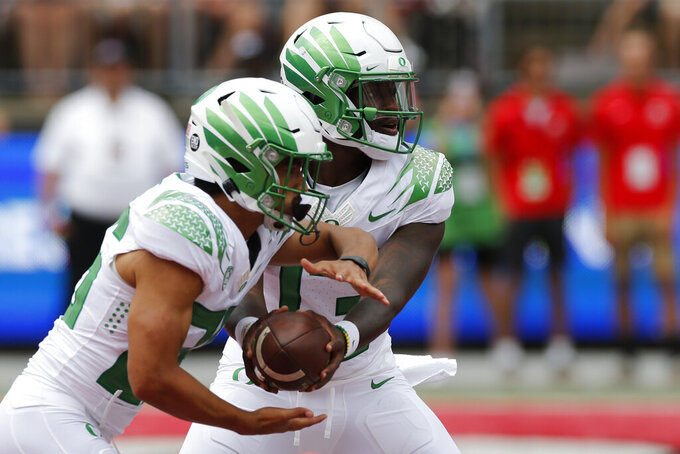 Oregon quarterback Anthony Brown, right, hands off to running back Travis Dye during the first half of an NCAA college football game Saturday, Sept. 11, 2021, in Columbus, Ohio. Oregon beat Ohio State 35-28. (AP Photo/Jay LaPrete)