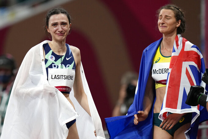Mariya Lasitskene, left, of Russian Olympic Committee, reacts after winning the women's high jump final, with silver medalist Nicola Mcdermott, of Australia, at the 2020 Summer Olympics, Saturday, Aug. 7, 2021, in Tokyo. (AP Photo/Petr David Josek)