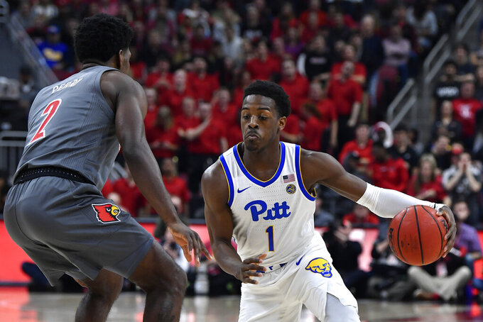 Pittsburgh guard Xavier Johnson (1) attempts to get around the defense of Louisville guard Darius Perry (2) during the first half of an NCAA college basketball game in Louisville, Ky., Friday, Dec. 6, 2019. (AP Photo/Timothy D. Easley)