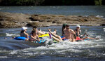 A group of people on inner tubes go through a small rapid on the Willamette River, Tuesday, June 11, 2019, near Springfield, Ore. Temperatures led area residents to seek relief from the heat by venturing to waterways and lakes, but officials are reminding people to remember to take appropriate safety precautions including wearing life preservers, if floating the river. (Andy Nelson/The Register-Guard via AP)