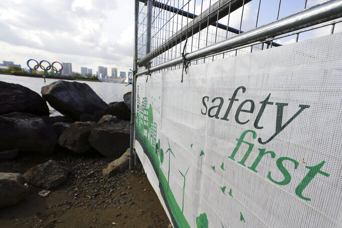 """A construction fence featuring the words """"Safety First"""" with a backdrop of the Olympic rings floating in the water in the Odaiba section Thursday, April 8, 2021, in Tokyo. The Tokyo Olympics are getting closer and things are starting to stir around the venues, though not as much as you might expect. Many preparations are still up in the air as organizers try to figure out how to hold the postponed games in the middle of a pandemic. (AP Photo/Eugene Hoshiko)"""
