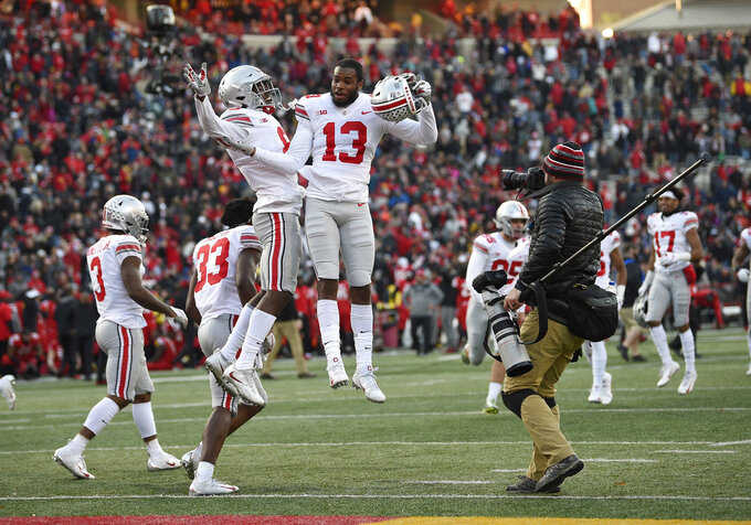 Ohio State cornerbacks Tyreke Johnson (13) and Kendall Sheffield, left center, celebrate after an NCAA football game against Maryland, Saturday, Nov. 17, 2018, in College Park, Md. Ohio State won 52-51 in overtime. (AP Photo/Nick Wass)