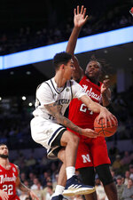 Georgia Tech guard Michael Devoe, left, passes around Nebraska forward Yvan Ouedraogo, right, in the first half of an NCAA college basketball game Wednesday, Dec. 4, 2019, in Atlanta. (AP Photo/John Bazemore)