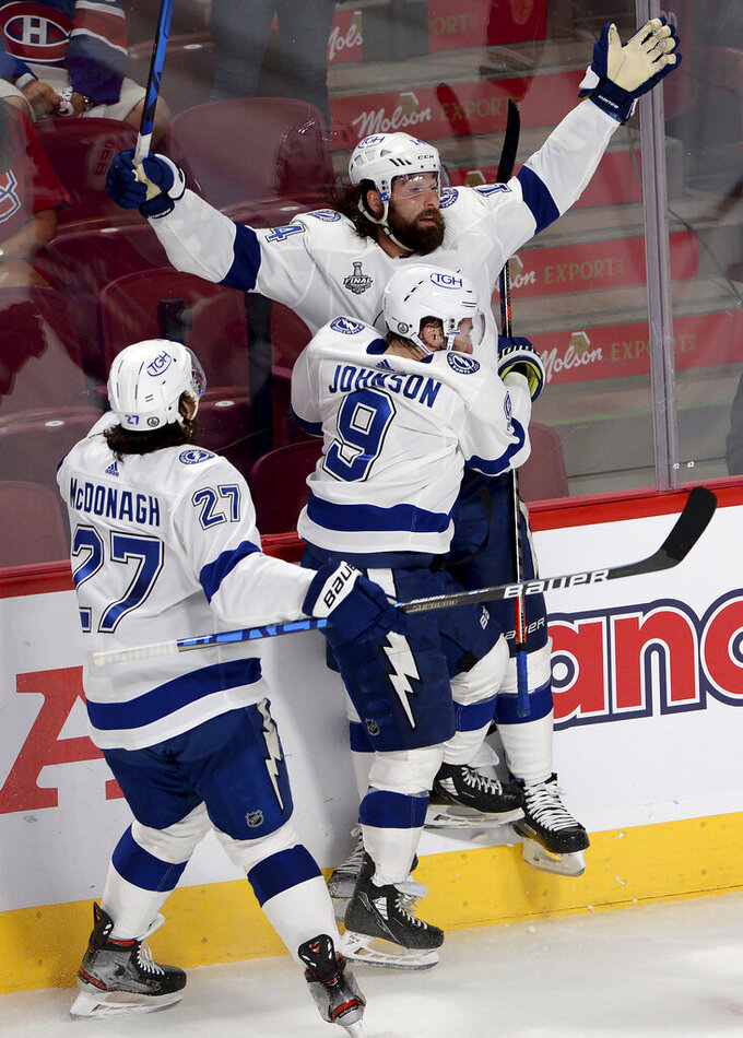 Tampa Bay Lightning's Pat Maroon (14) celebrates his goal with teammates Ryan McDonagh (27) and Tyler Johnson (9) during the third period of Game 4 of the NHL hockey Stanley Cup final against the Montreal Canadiens in Montreal, Monday, July 5, 2021. (Ryan Remiorz/The Canadian Press via AP)