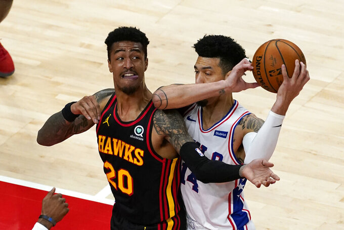 Philadelphia 76ers forward Danny Green (14) and Atlanta Hawks forward John Collins (20) battle for the ball during the first half of an NBA basketball game Monday, Jan. 11, 2021, in Atlanta. (AP Photo/John Bazemore)