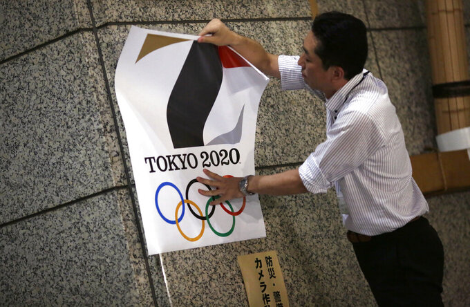 FILE - In this Sept. 1, 2015, file photo, a poster with the logo of Tokyo 2020 Olympic Games is removed from a wall by a worker during an event staged for photographers at the Tokyo Metropolitan Government building in Tokyo. Tokyo Olympic organizers decided to scrap the logo for the 2020 Games following another allegation its Japanese designer might have used copied materials. (AP Photo/Eugene Hoshiko, File)