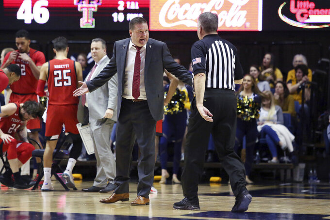 Texas Tech coach Chris Beard, center left, speaks with an official during the second half of an NCAA college basketball game against West Virginia, Saturday, Jan. 11, 2020, in Morgantown, W.Va. (AP Photo/Kathleen Batten)