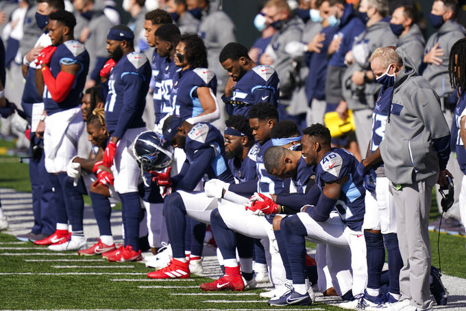 Tennessee Titans players take a knee during the national anthem before an NFL football game against the Cincinnati Bengals, Sunday, Nov. 1, 2020, in Cincinnati. (AP Photo/Bryan Woolston)