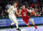 Louisville guard Ryan McMahon (30) drives to the basket as Miami guard Dejan Vasiljevic (1) defends during the first half of an NCAA college basketball game, Tuesday, Nov. 5, 2019, in Coral Gables, Fla. (AP Photo/Lynne Sladky)