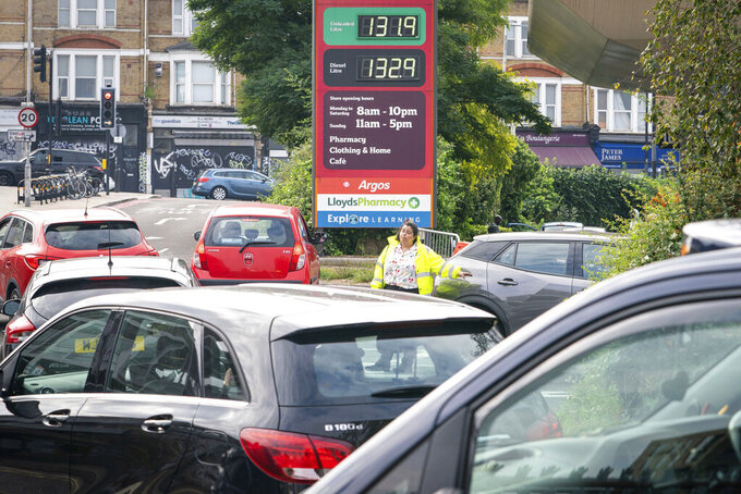 A member of staff directs drivers in a queue for fuel at a closed Sainsbury's petrol station in south London, Sunday, Sept. 26, 2021. In a U-turn, Britain says it will issue thousands of emergency visas to foreign truck drivers to help fix supply-chain problems that have caused empty supermarket shelves, long lines at gas stations and shuttered petrol pumps.  (Dominic Lipinski/PA via AP)