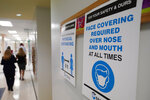 Signs in a hallway reminds students to wear masks and distance themselves at Fox Trail Elementary School, Friday, Oct. 9, 2020, in Davie, Fla. Broward County, Florida schools began a phased reopening for face-to-face eLearning Friday. (AP Photo/Wilfredo Lee)