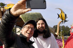 John Wierick, left, takes a picture with Matthew Nolte, who was portraying Jesus on the Lutheran Laymen's League float, before the 131st Rose Parade in Pasadena, Calif., Wednesday, Jan. 1, 2020. (AP Photo/Michael Owen Baker)