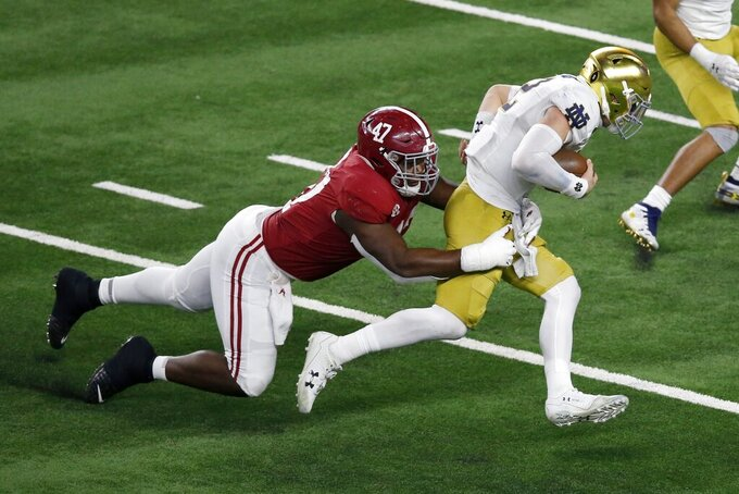 Notre Dame quarterback Ian Book (12) is sacked by Alabama defensive lineman Byron Young (47) in the second half of the Rose Bowl NCAA college football game in Arlington, Texas, Friday, Jan. 1, 2021. (AP Photo/Roger Steinman)