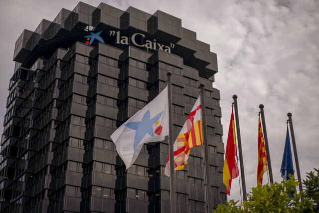 A view of the CaixaBank headquarter in Barcelona, Spain, Thursday, Sept. 17, 2020. Two of Spain's biggest banks are poised to merge and create the country's largest bank in terms of domestic operations, with assets of more than 600 billion euros (dollars 708 billion). The deal brings the prospect of more job losses amid difficult times for the financial sector. A tie-up between CaixaBank, the largest bank in the domestic market, and Bankia, Spain's biggest mortgage lender, could herald other moves toward consolidation in the financial sector. (AP Photo/Emilio Morenatti)