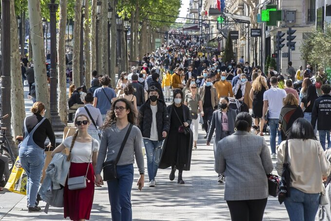 FILE - In this Saturday, May 16, 2020 file photo people wear face masks to help curb the spread of the coronavirus stroll along the Champs Elysees avenue in Paris. Britain will require all people arriving from France to isolate for 14 days - an announcement that throws the plans of tens of thousands of holiday makers into chaos. The government said late Thursday Aug. 13, 2020 that France is being removed from the list of nations exempted from quarantine requirements because of a rising number of coronavirus infections, which have surged by 66% in the past week. (AP Photo/Michel Euler, File)