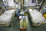 In this Thursday, Feb. 6, 2020, photo, a medical worker monitors patients in the isolated intensive care unit at a hospital in Wuhan in central China's Hubei province. China's virus death toll have surpassed the number of fatalities in the 2002-03 SARS epidemic, but fewer new cases were reported in a possible sign its spread might be slowing as other nations stepped up efforts to block the disease. (Chinatopix via AP)
