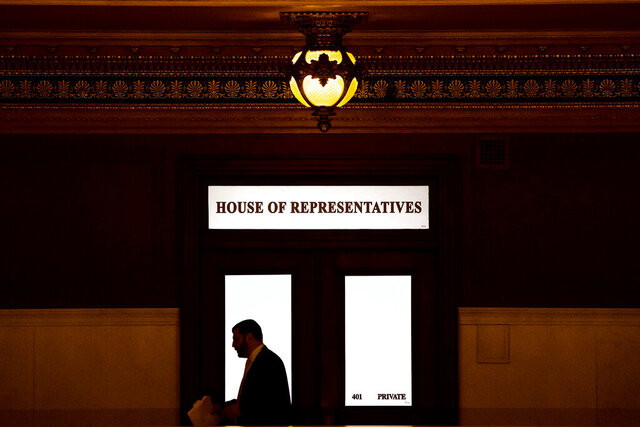 FILE - In this Nov. 20, 2019 file photo, a lawmaker is silhouetted as he walks past a window in the Pennsylvania Capitol in Harrisburg, Pa. While most states have not yet considered law changes to screen former clergy members who seek licenses for jobs that put them in contact with children, at least 20 state attorneys general are conducting investigations of how church officials handled abuse allegations, including reporting them to civil law enforcement, largely in the wake of the Pennsylvania attorney general office's 2018 grand jury report that looked at how abuse allegations were handled in six dioceses. (AP Photo/Matt Rourke, File)