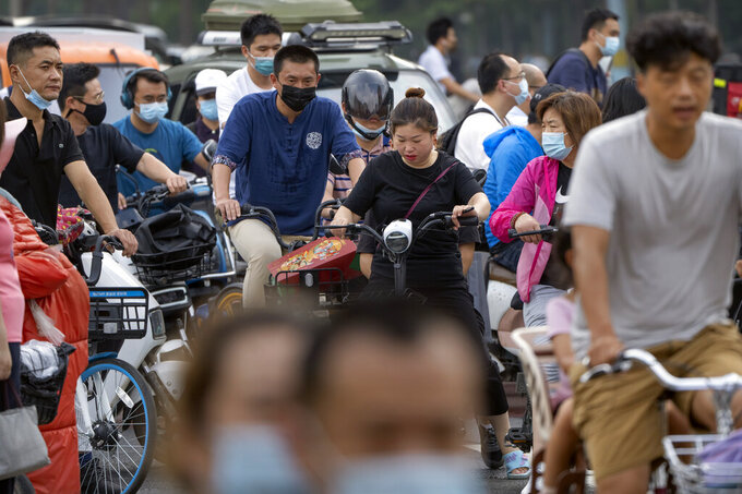 People wearing face masks to protect against COVID-19 ride bicycles across an intersection during the morning rush hour in Beijing, Wednesday, Aug. 4, 2021. The coronavirus's delta variant is challenging China's costly strategy of isolating cities, prompting warnings that Chinese leaders who were confident they could keep the virus out of the country need a less disruptive approach. (AP Photo/Mark Schiefelbein)