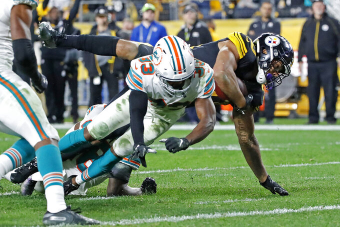 Pittsburgh Steelers running back James Conner, right, dives for the end zone for a touchdown with Miami Dolphins cornerback Jomal Wiltz (33) defending during the second half of an NFL football game in Pittsburgh, Monday, Oct. 28, 2019. (AP Photo/Don Wright)