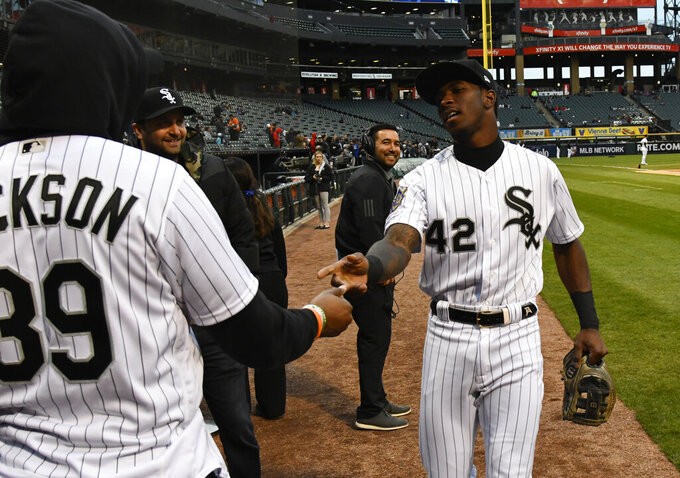 Chicago Bears player Eddie Jackson, left, and Chicago White Sox shortstop Tim Anderson, right, shake hands before Jackson threw out a ceremonial first pitch before a baseball game between the White Sox and the Kansas City Royals, Monday, April 15, 2019, in Chicago. No. 42 was worn to honor Jackie Robinson. (AP Photo/Matt Marton)